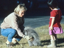 Woman holding a porcupine in front of little girl