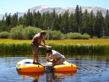 Two researchers coring a lake